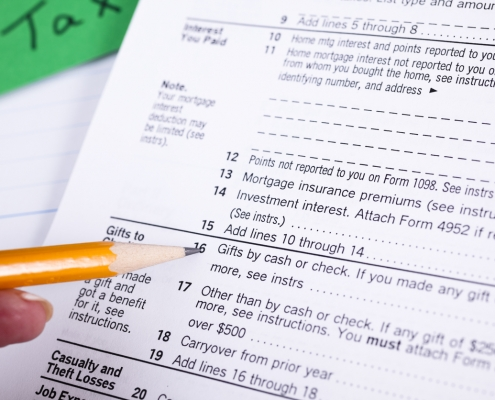 pencil in hand pointing to a list of itemized deductions on a tax form