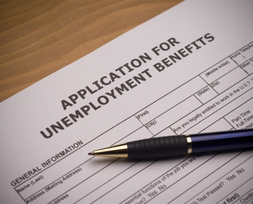 application for unemployment benefits on a desk with a pen on top