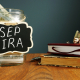 SEP IRA written on a jar of money on a table with books and glasses