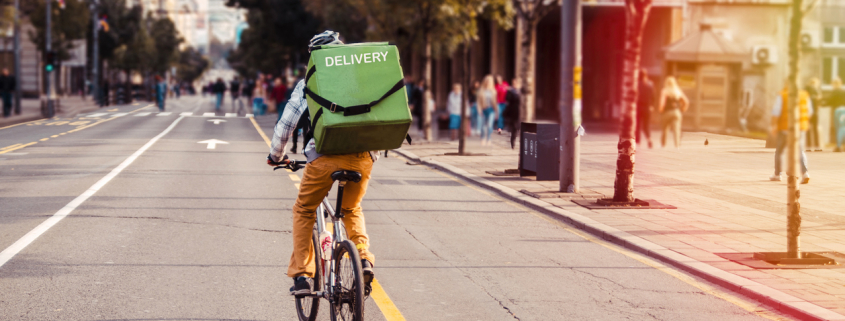 a gig worker riding his bike to a delivery