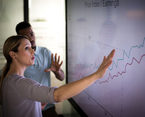 businessman and businesswoman looking at a graph on a screen