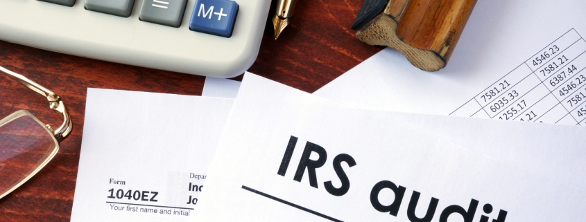 a desk with tax forms, a calculator, glasses, and a form saying irs audit