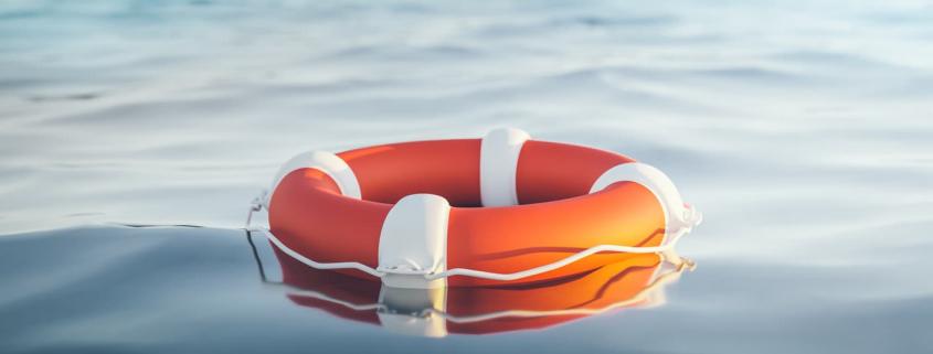 orange life raft floating in water